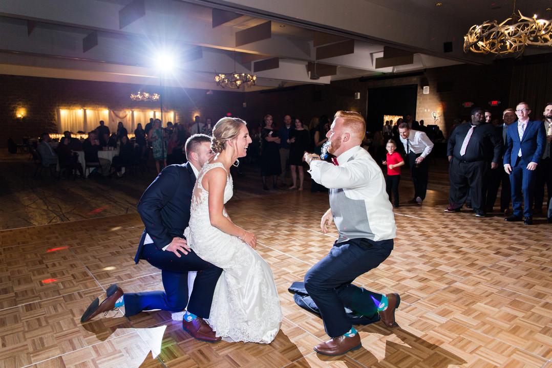 backlit rim light during garter removal at wedding reception with bride on best mans knee