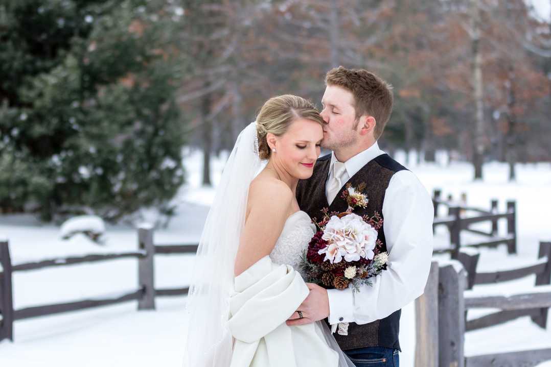 groom kissing brides cheek during snowy wedding portrait in front of fence