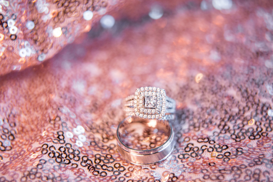 macro wedding rings with blurred out pink sequins in background