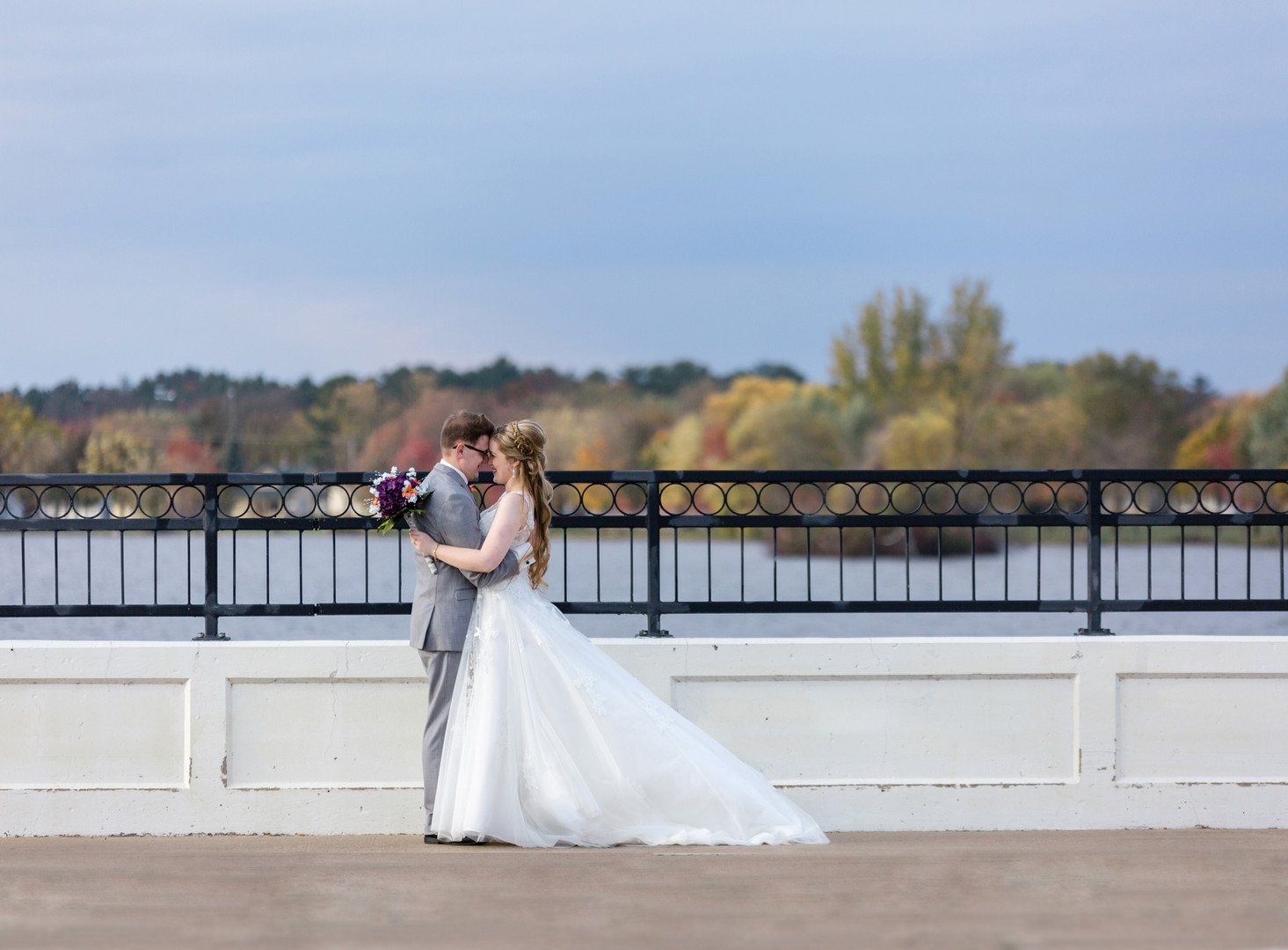 bride and groom wedding portrait on stevens point bridge overlooking water and fall trees foilage