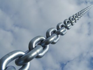 Length of steel chain diminishing in size from bottom left corner to top right on a cloudy sky background