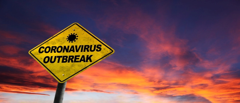 A diamond-shaped road sign reading CORONAVIRUS OUTBREAK seen against a fiery orange sky