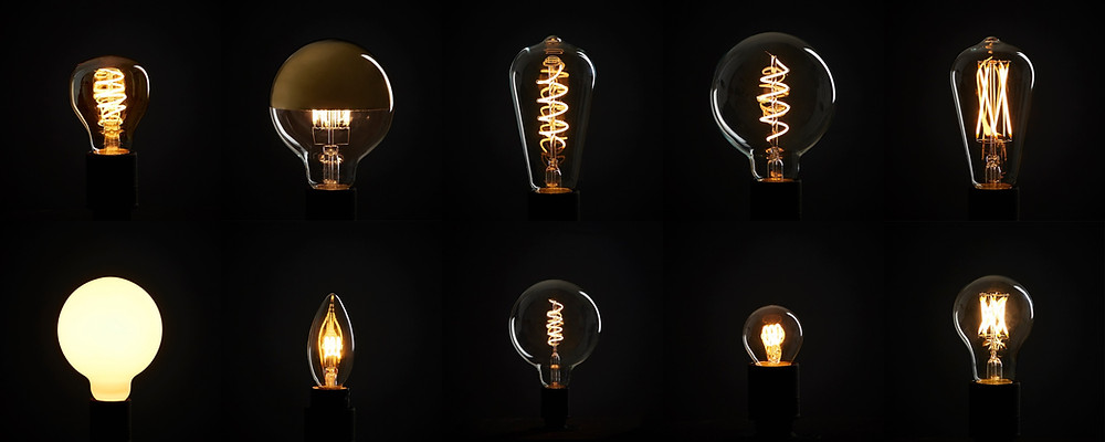 Two rows of five cordless warmly glowing light bulbs suspended on black background