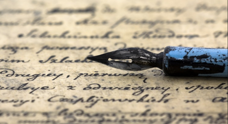 A close-up image of a tarnished fountain pen on a sheet of paper written on in a beautiful caligraphied hand