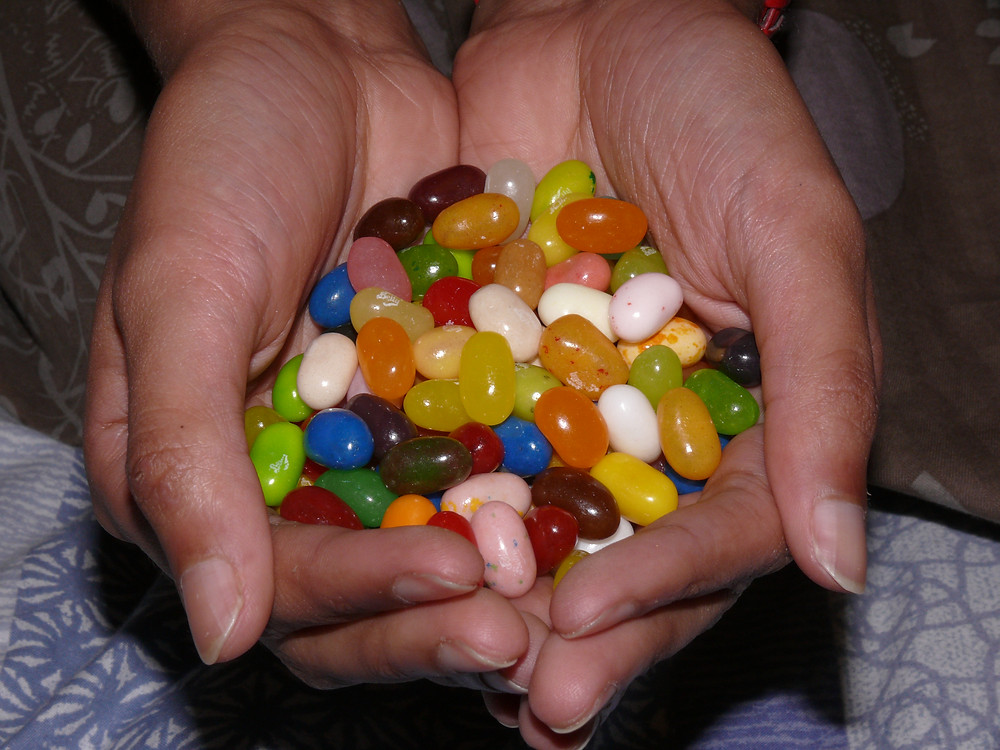 A heap of colourful jellybeans cupped in a pair of hands