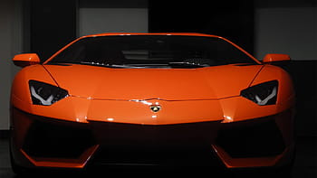Gleaming orange Lamborghini seen face on