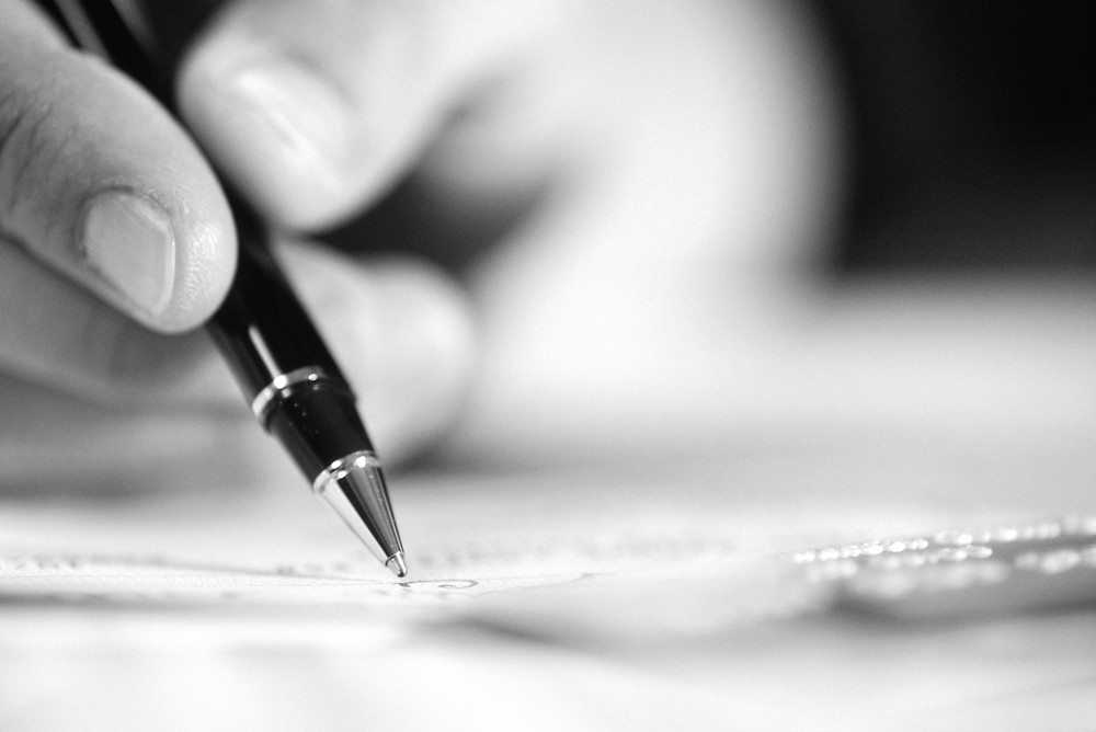 A monochrome close-up of thumb and fingers holding a pen and poised over of a sheet of paper