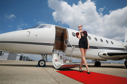 Woman-standing-on-red-carpet-upon-exiting-private-jet