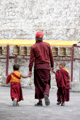 Two child monks lead in the school by a senior monk
