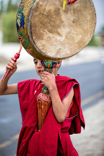 A young monk leading a procession in the village