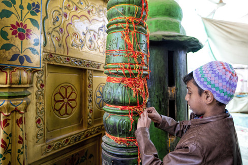 Tying the yellow and orange thread at the dargah