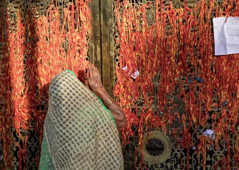 A hindu lady prays at the dargah