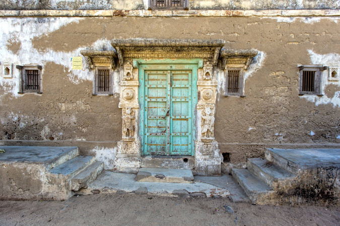 A Wooden door encased in cement and surrounded by pillars with carving on them.