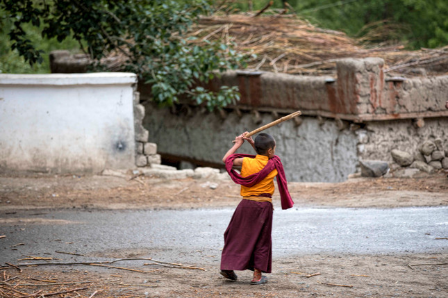 A young monk playing with a make shift bat