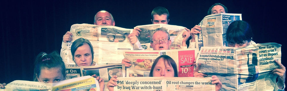 Leo Dance Company peering over newspapers, in performance of 'Miss-read'