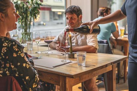 Wein wird eingeschenkt bei Gästen am Tisch im Restaurant Libelle