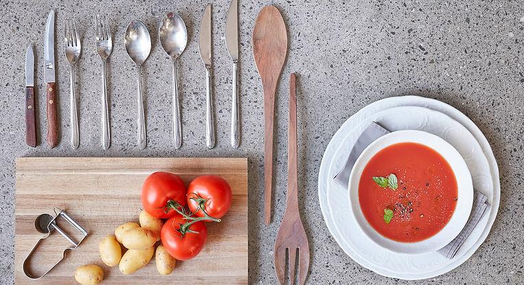 Kochzutaten, Besteck und ein Teller Tomatensuppe liegen arrangiert auf dem Boden