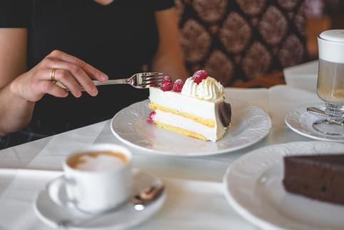 Gast mit einem Stück Torte und Kaffee