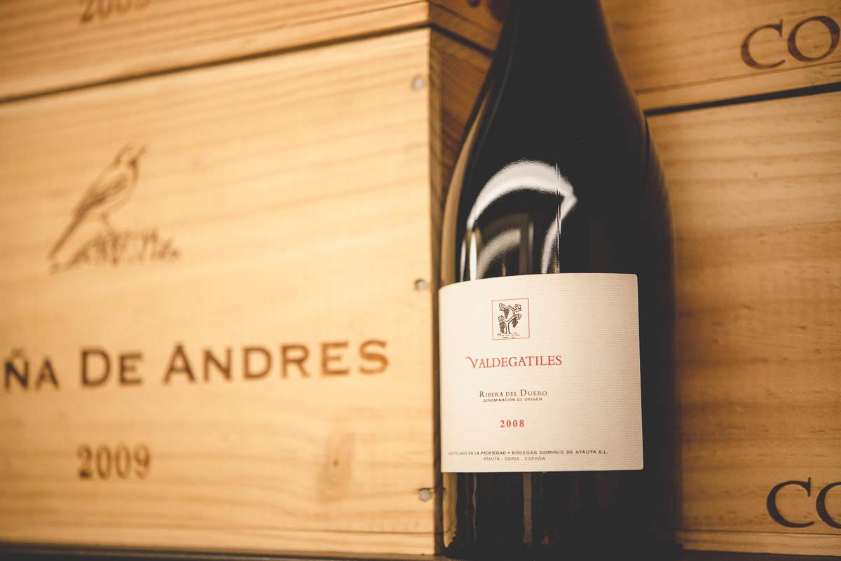 Eine Flasche Wein neben Weinkisten