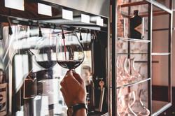 Weinglas wird am Enomat mit Rotwein gefüllt
