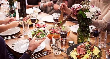 Gäste bei einer Tavolata mit verschiedenen Speisen und Wein