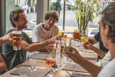 Junge Männer beim Anstossen im Restaurant Libelle