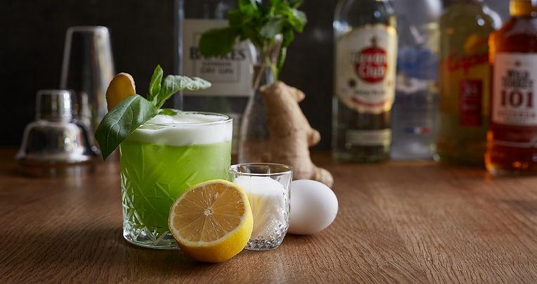 Cocktail mit Zutaten und verschiedenen Flaschen im Hintergrund