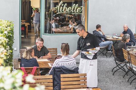 Blick auf die Terrasse wo gerade Essen serviert wird im Restaurant Libelle