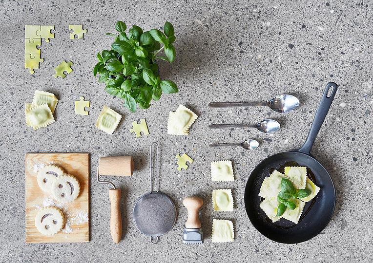 Ravioli und Kochutensilien liegen arrangiert auf dem Boden