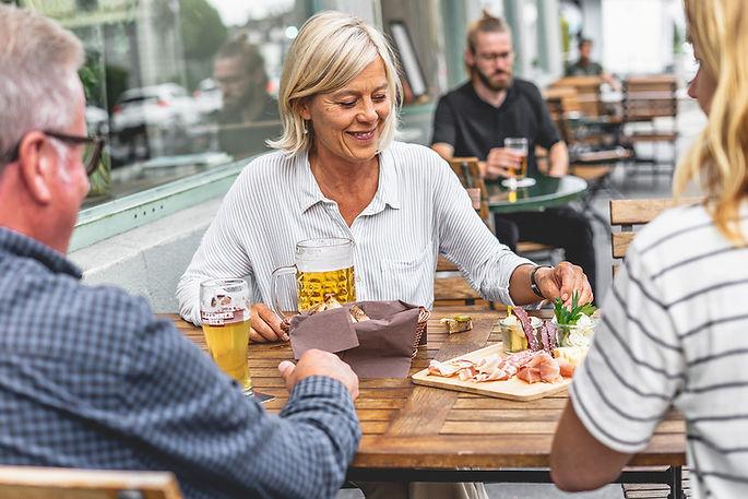 Zwei Frauen und ein Mann mit Apéro-Plättli und Bier bei den Aussensitzplätzen vom Restaurant Libelle