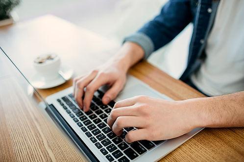Mann arbeitet am Macbook und trinkt Kaffee