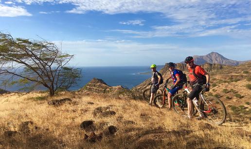 Drei Biker stehen auf einem Hügel und im Hintergrund das Meer