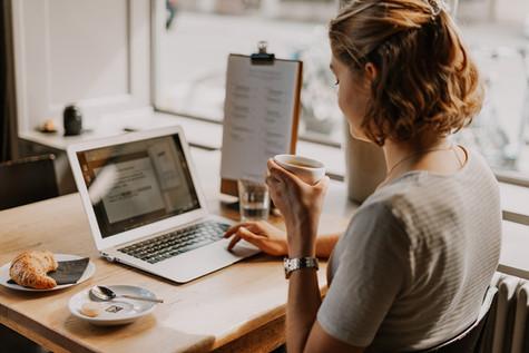 Junge Frau beim Arbeiten und Kaffee trinken im Restaurant Libelle