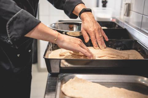 Koch bei der Zubereitung von Wiener Schnitzel