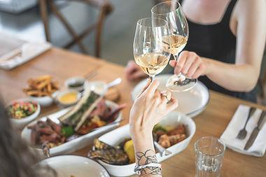 Gäste stossen mit Weisswein an, auf dem Tischen steht Essen
