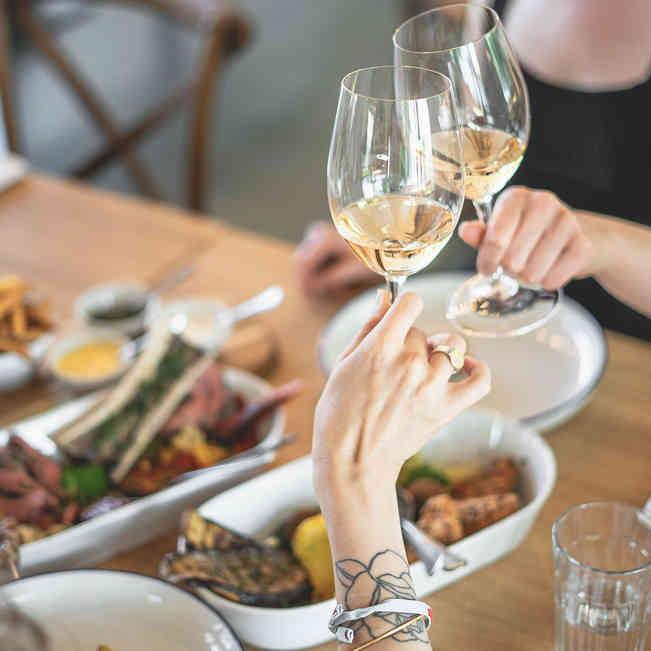 Seehaus Grill Luzern - Gäste beim Anstossen mit Wein und auf dem Tisch verschiedene Grillspezialitäten