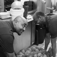 Köche heben Kartoffelsack hoch in der Küchs