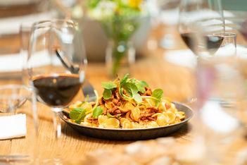 Gedeckter Tisch mit Nudelgericht in Pfanne und einem Glas Rotwein