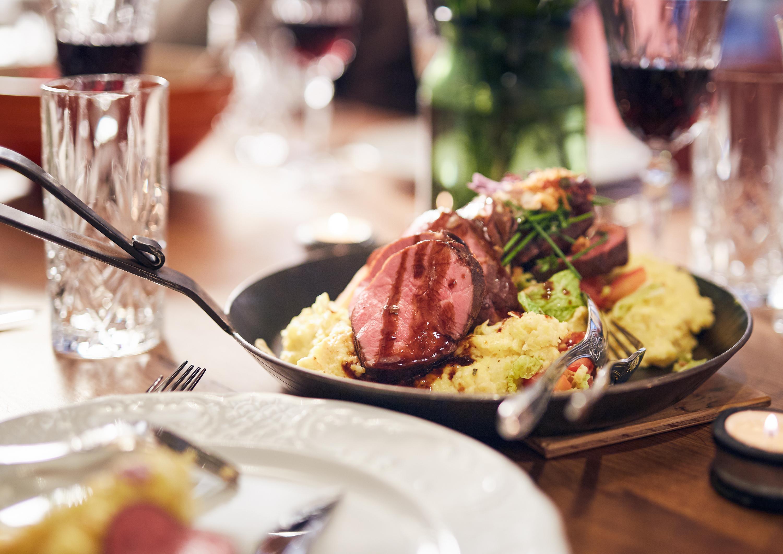 Fleischgericht mit Beilagen und Saucen in einer Gusseisenpfanne serviert