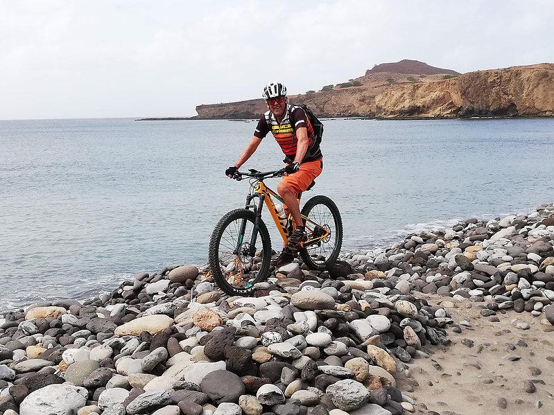Biker am Strand mit Mietbike von TrailTravel