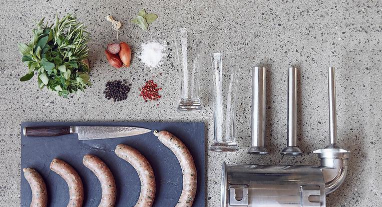 Wurst-Werkstatt - Gewürze, fertige Würste und Utensilien zum Wursten liegen arrangiert auf dem Boden