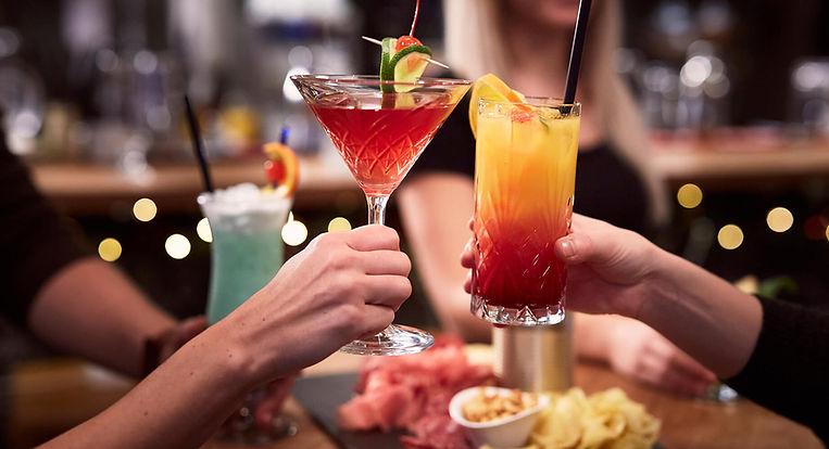 Cocktail-Apéro - Zwei Gäste stossen mit farbigen Cocktails an