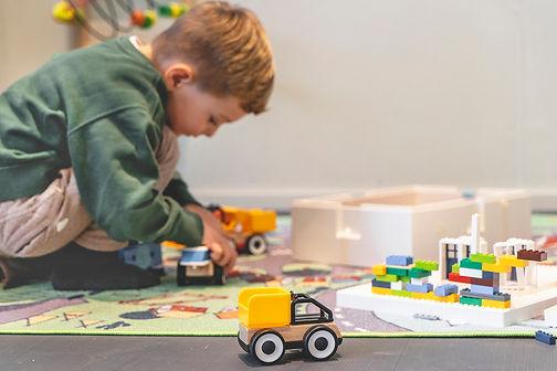 Kind spielt auf Spielteppich mit Autos und Lego