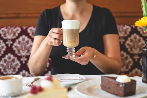 Gast mit Kaffee Spezialität und einem Stück Sachertorte