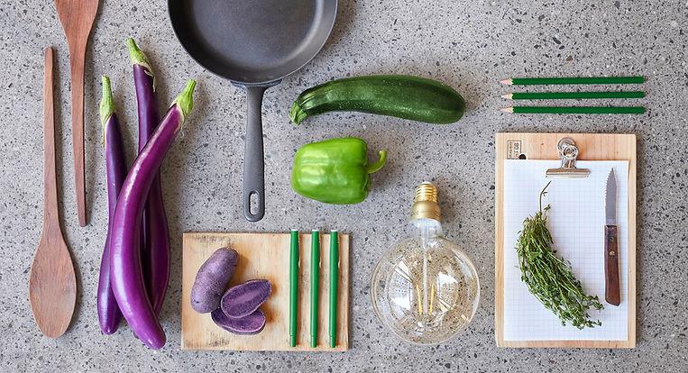 Team-Werk - Gemüse, eine Pfanne und Schreibutensilien liegen arrangiert auf dem Boden
