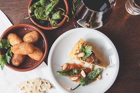 Verschiedene Tapas Gerichte und Rotwein auf einem Tisch
