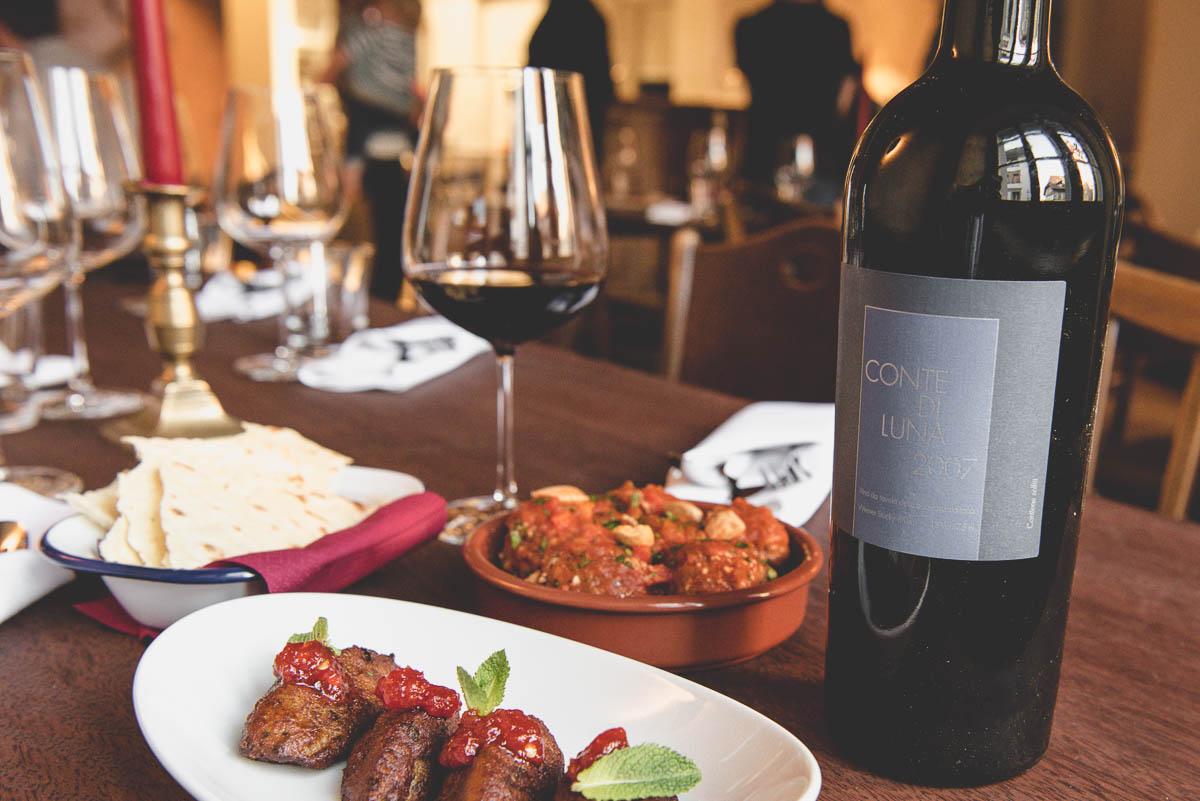 Verschiedene Gerichte und eine Flasche Wein