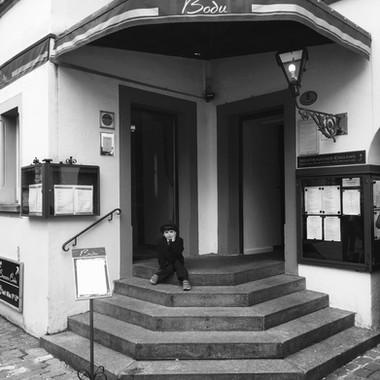 Junge sitzt auf der Treppe beim Eingang Brasserie Bodu