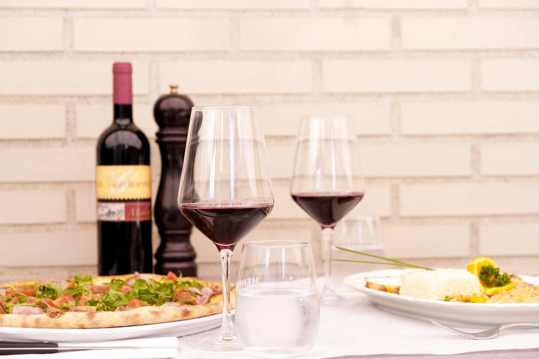 Tavola imbandita con pizza e vino
