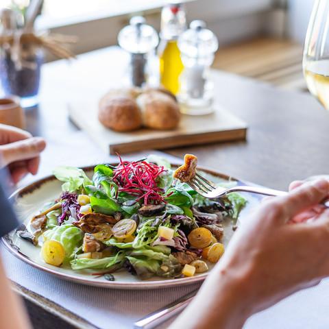 Frau isst Salat mit Trauben und Feigen im Seerestaurant Kastanienbaum